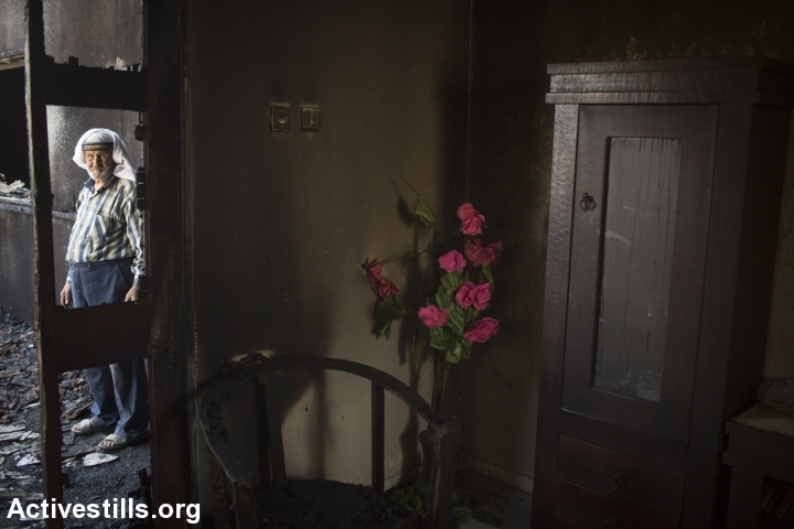The Dawabshe grandfather stands in the charred home in which his family members were murdered by extremist Jewish settlers, Duma, West Bank, July 31, 2015. (Oren Ziv/Activestills.org)