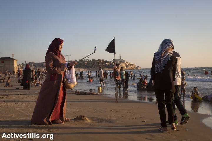 Palestinian citizens and residents of Israel at the beach in Tel Aviv, with the Old City of Jaffa in the background, July 7, 2016. (Oren Ziv/Activestills.org)