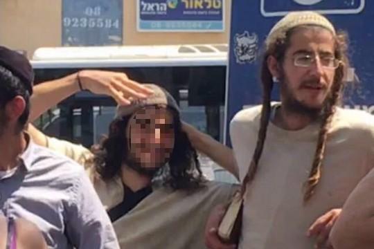 Young Israeli settlers make a three-finger gesture toward the Dawabshe family outside the court in Lod. (Hiyam Zabarka)