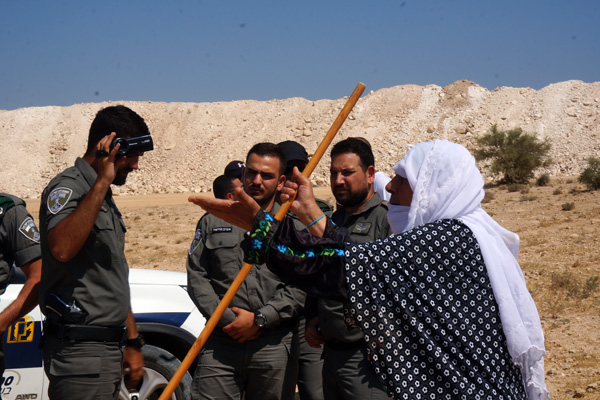 An elderly Bedouin woman from the unrecognized village of Umm el-Hiran argues with Israeli police officers as construction crews prepare to fence in the village's homes, July 31, 2016. (Negev Coexistence Forum for Civil Equality)