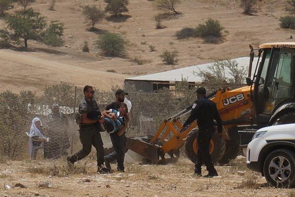 Police arrest a youth from Umm el-Hiran as construction crews prepare to build a fence around village homes, July 31, 2016. (Negev Coexistence Forum for Civil Equality)