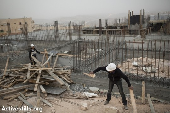 Palestinian construction workers work at a site in Jerusalem's Ramat Shlomo neighborhood. (Tali Mayer/Activestills.org)