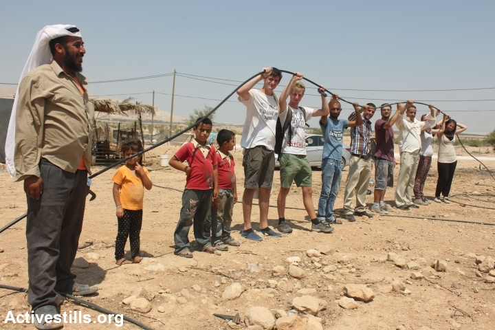 Palestinians and international activists connect a water pipe to Palestinian families' homes in Fasayil, Jordan Valley, August 17, 2013. (Ahmad Al-Bazz/Activestills.org)