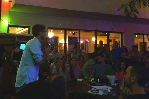 Iyad Othmani speaks to a crowd of Israelis in a Tel Aviv bar. (Ihab Sayag)