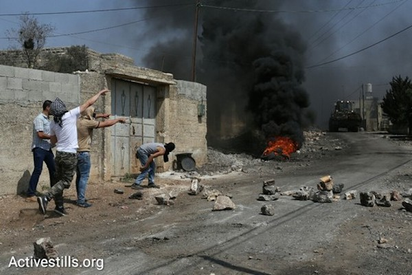 Burning tires and stones during the weekly protest in Kafr Qaddum. August, 28, 2016. (Oren Ziv/Activestills.org)