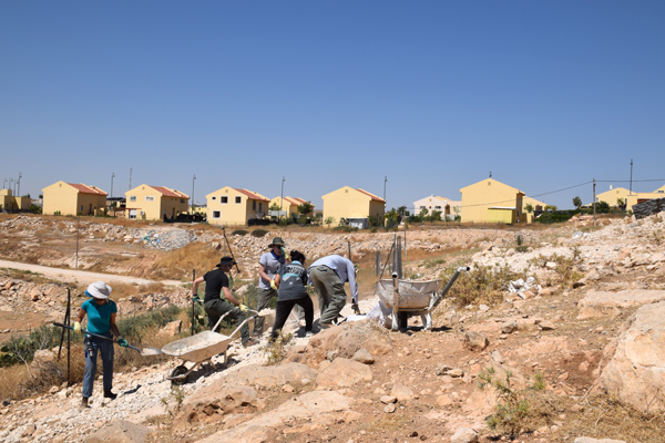 A delegation from the Center for Jewish Nonviolence helps rebuild a demolished home in the Palestinian village of Umm el-Kheir, July 12, 2016. The Israeli settlement of Carmel is seen in the background. (Michael Schaeffer Omer-Man)