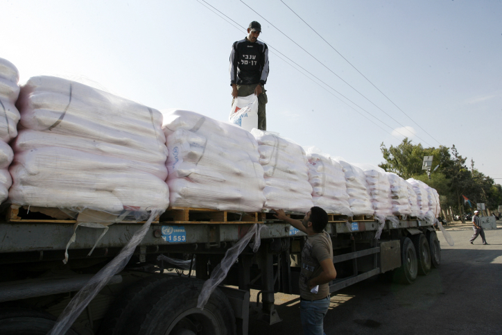File photo of Palestinian workers offloading a truck full of aid in the Gaza Strip. (Abed Rahim Khatib/Flash90)