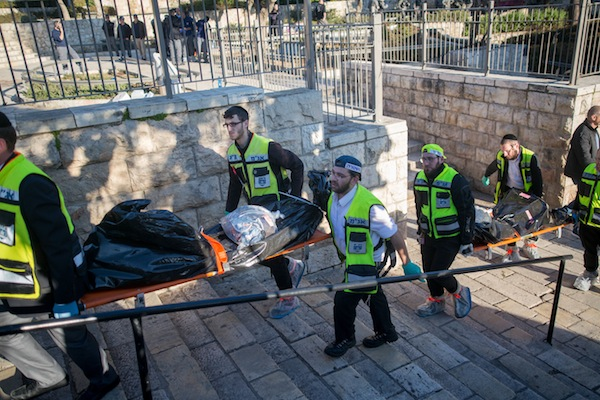 Zaka rescue personnel carry the bodies of Palestinian attackers at the scene of a shooting and stabbing attack near Damascus Gate, Jerusalem, February 3, 2016. Three Israelis were wounded, two critically and one lightly, after being stabbed by three Palestinian attackers, who were shot and killed by Israeli security forces at the scene. Photo by Yonatan Sindel/Flash90)