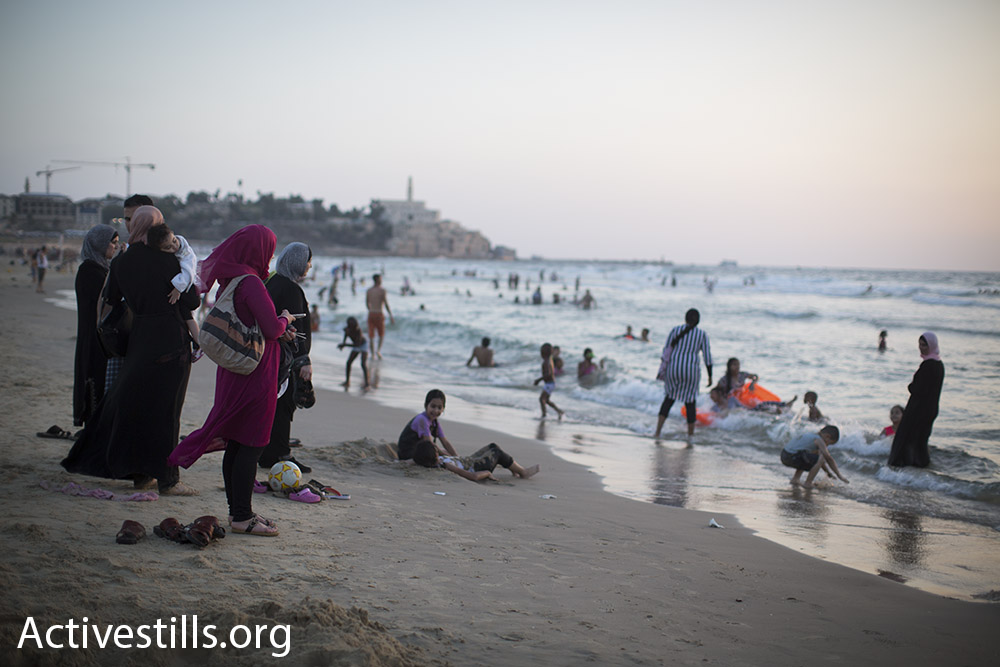 Palestinian women watch their relatives swim in the sea just north of Jaffa during Eid al-Adha, September 14, 2016. (Oren Ziv/Activestills.org) Women are more likely to receive entry permits from Israeli military authorities, young men are often excluded from holiday permits.