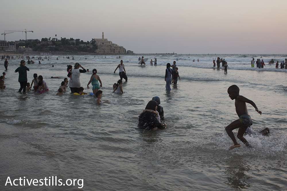 Palestinians from West Bank swim in the sea just north of Jaffa during Eid al-Adha, September 14, 2016. (Oren Ziv/Activestills.org)