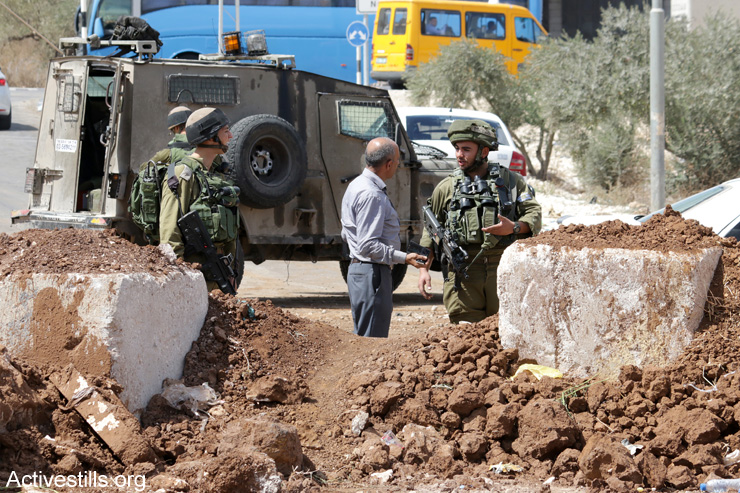 Palestinians from the village of Beita hold Friday prayers at an Israeli military roadblock in protest of the collective punishment, September 23, 2016. (Ahmad Al-Bazz / Activestills.org)