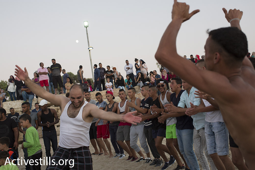 Young Palestinian men dance on the beach in Jaffa during Eid al-Adha, September 14, 2016. (Oren Ziv/Activestills.org)