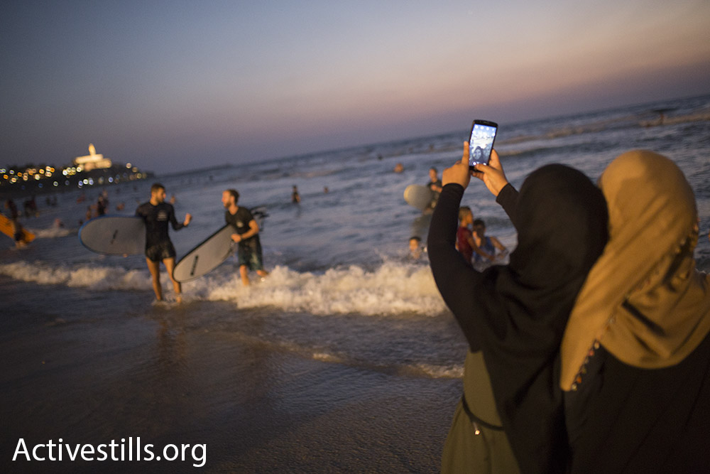 Palestinian women take a selfie on the beach north of Jaffa during Eid al-Adha as two Israeli surfers exit the water, September 14, 2016. (Oren Ziv/Activestills.org)
