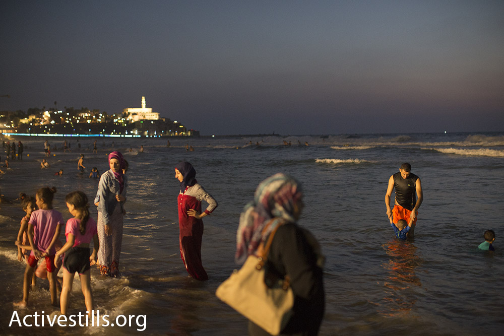 Palestinian women and children wade in the sea during Eid al-Adha, September 14, 2016. (Oren Ziv/Activestills.org) The Old City of Jaffa is seen in the background.