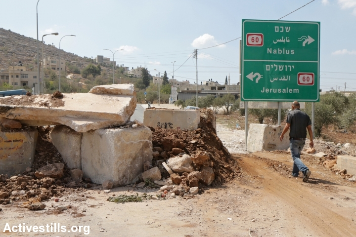 A Palestinian man passes by an Israeli army roadblock made of concrete, dirt and debris at the main entrance to the West Bank village of Beita, September 5, 2016. (Ahmad Al-Bazz/Activestills.org)
