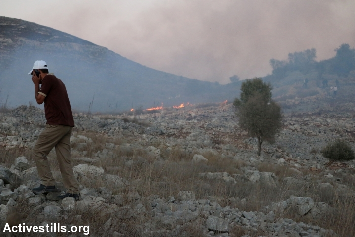 Palestinian farmers clash with Israeli settlers after they set fire to Palestinian agricultural fields in Burin village near Nablus, October 3, 2015. (Ahmad Al-Bazz/Activestills.org)