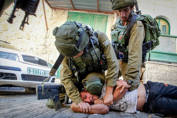 Israeli soldiers detain a Palestinian man following a house raid in the West Bank city of Hebron September 20, 2016. (Wisam Hashlamoun/Flash90)