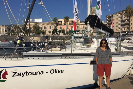 +972 blogger Orly Noy stands alongside the 'Zaytouna,' which sailed to Gaza as part of an all-women aid flotilla.