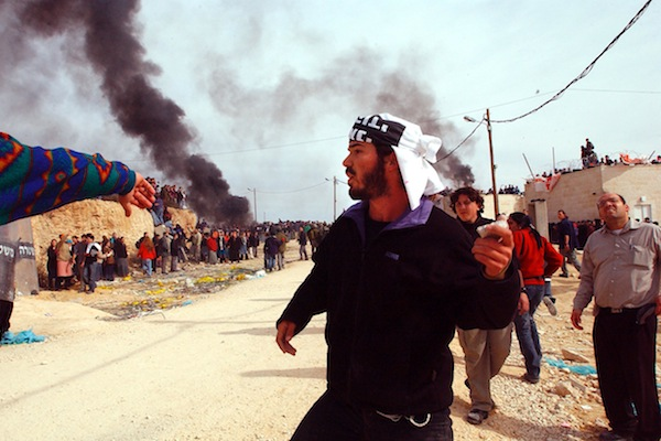 An Israeli settler throws stones at armed forces in the illegal outpost of Amona, Jan. 1, 2006 (file photo). Clashes broke out shortly after the High Court gave the green light to dismantle half a dozen homes in the area. (Yossi Zamir/Flash90)