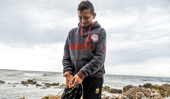 Abdel-Salam, a child laborer in Gaza, holds a fishing net. (Mohammad Abu Rukbeh/DCIP)