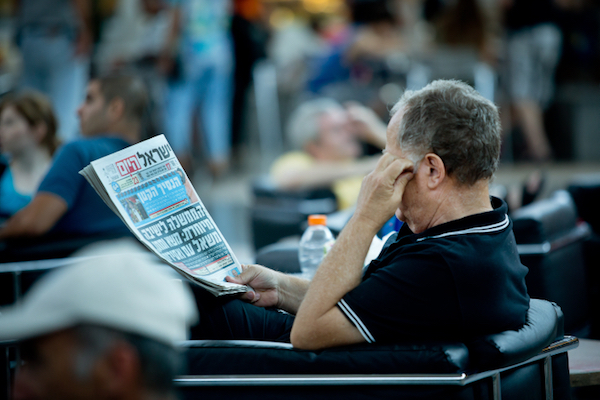Illustrative photo of a man reading an Israeli newspaper at the airport. (Moshe Shai/Flash90)