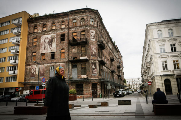 A Polish woman walks by Prozna Street in Warsaw, a part of the former Jewish quarter that escaped destruction during World War II. (Miriam Alster/FLASH90)