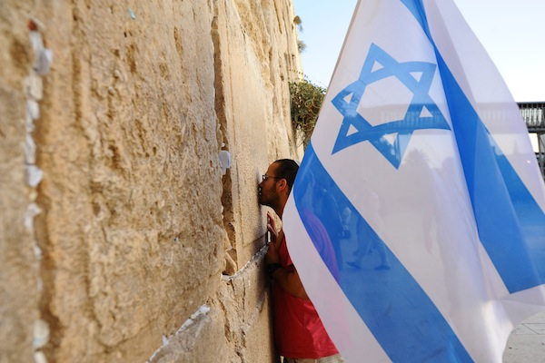 A man holds an Israeli flag during a march in support of the city of Jerusalem at the Western Wall, Jerusalem's Old City on October 22, 2015, following a wave of attacks by Palestinians. (Mendy Hechtman/Flash90)