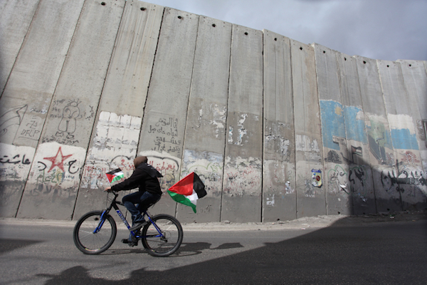 A Palestinian youth rides a bicycle adorned with Palestinian flags past the Israeli separation wall near Jerusalem. (Issam Rimawi/Flash90)
