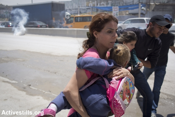 Palestinian parents whisk their children away from clashes between Israeli forces and Palestinian youth at the Qalandiya checkpoint separating Ramallah and Jerusalem, May 15, 2014. (Oren Ziv/Activestills.org)