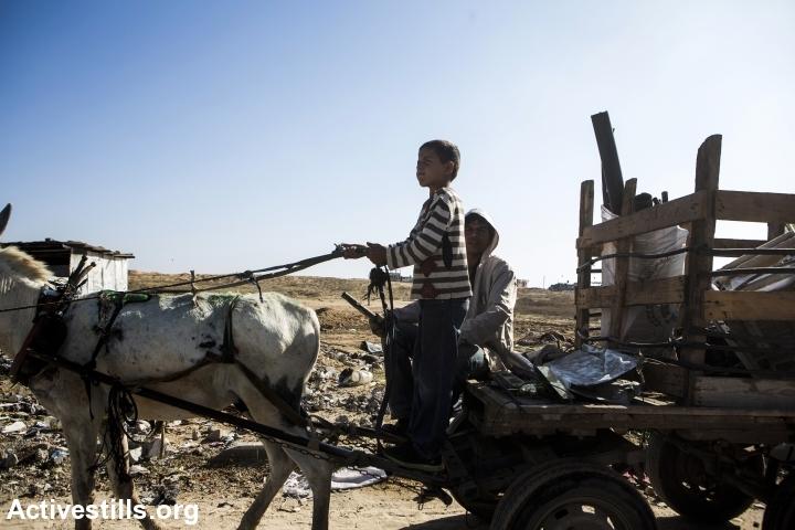 Palestinian children collect scrap metal and materials after Israel's 2014 assault on the Gaza Strip, Beit Hanoun, Gaza Strip, November 9, 2014. (Anne Paq/Activestills.org)