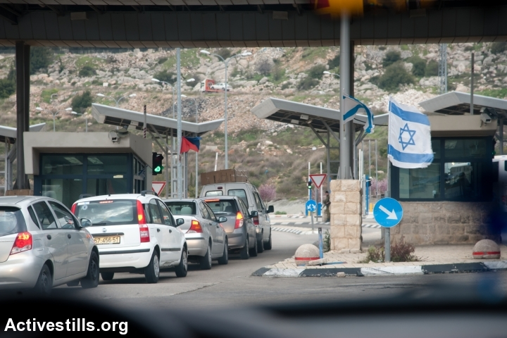 Cars with yellow, Israeli license plates drive through a settler bypass road near Bethlehem leading from the West Bank into Israel. Soldiers rarely stop cars at 'settler checkpoints.' (Ryan Rodrick Beiler/Activestills.org)