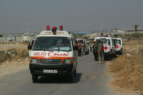 International Red Cross members try to secure an ambulance for ill Palestinians for transport to Israel as Israeli tanks stand watch, northern Gaza near the Erez Crossing, June 19, 2007. (Ahmad Khateib/Flash90)
