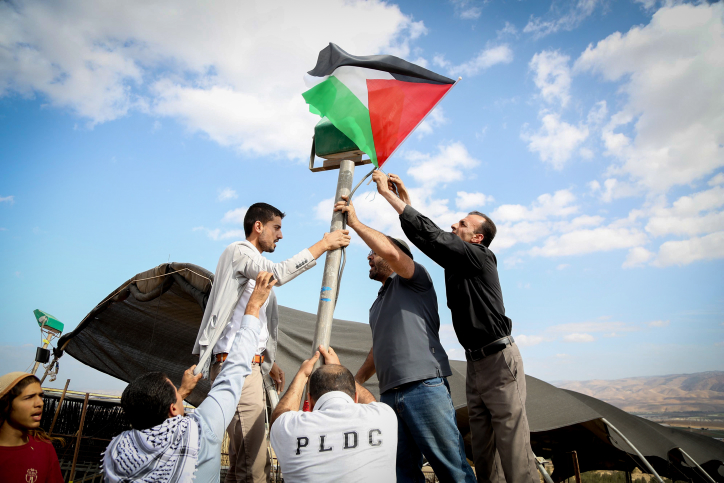 Palestinian activists raise a flag at the 'Yasser Arafat outpost,' a nonviolent action protesting two new Israeli settlement outposts in the area, Jordan Valley, West Bank, November 17, 2016. (Flash90)