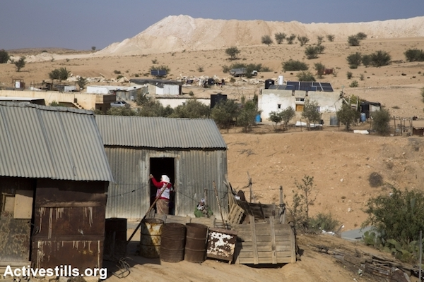 A Bedouin woman enters a tin shack in the unrecognized village of Umm el-Hiran, the Negev. November 22, 2016. Residents expected Israeli authorities to demolish the entire village a few hours earlier. (Keren Manor/Activestills.org)