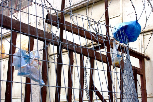 A used diaper and bag or urine thrown from the settlement above hang on a fence in the occupied city of Hebron. (Sarah Stern)