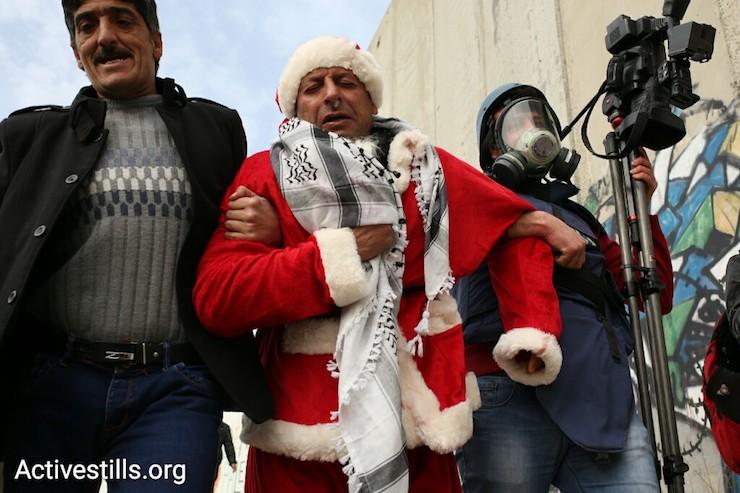 An injured protester is led away by other demonstrators, Bethlehem, West Bank, December 23, 2016. (Activestills)