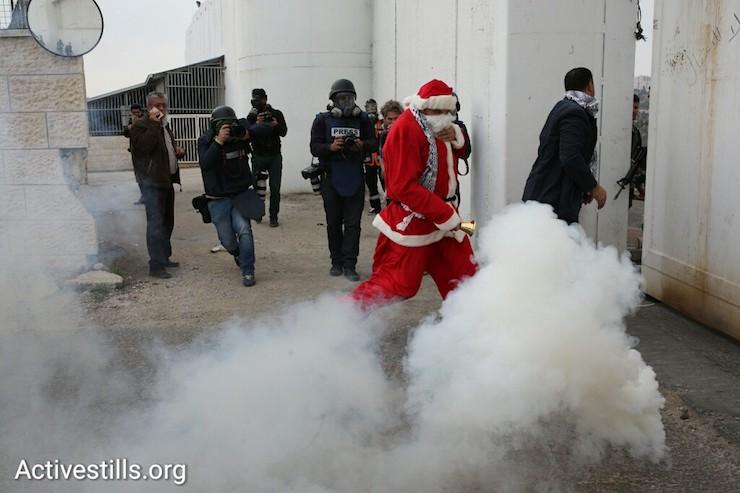 A protester dressed as Santa Claus runs from a cloud of tear gas shot by Israeli Border Police, Bethlehem, West Bank, December 23, 2016. (Activestills)
