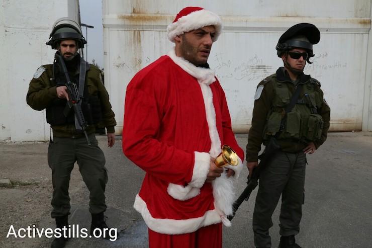 A protester dressed as Santa Claus stands in front of Israeli security forces, Bethlehem, West Bank, December 23, 2016. (Activestills)