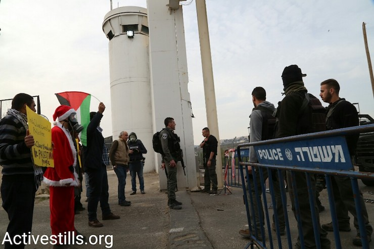 Protesters and Israeli security forces stand by one of Bethlehem's main checkpoints, West Bank, December 23, 2016. (Activestills)