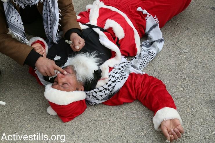 An injured protester is tended to by other demonstrators, Bethlehem, West Bank, December 23, 2016. (Activestills)