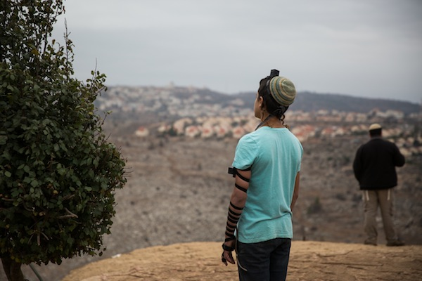 Young Jewish men pray at the Jewish settlement outpost of Amona in the West Bank, December 16, 2016. (Hadas Parush/Flash90)