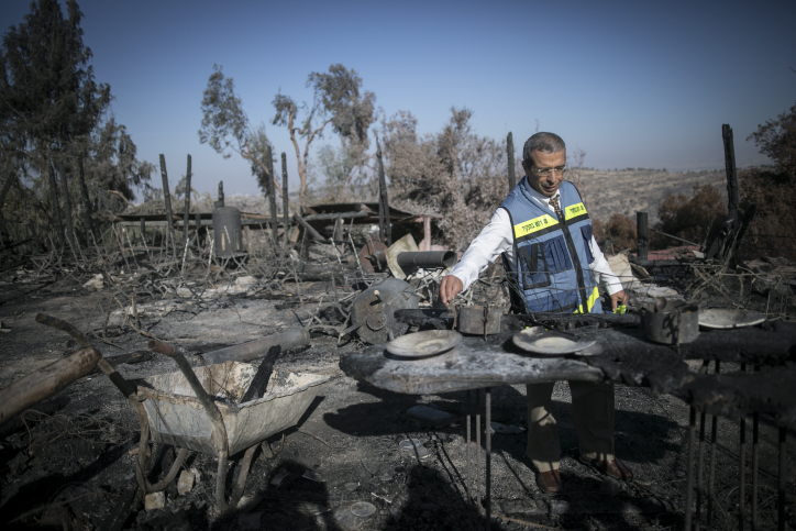 An Israeli Tax Authority worker checks the damage inspects the damage caused to Rama's Kitchen restaurant during a wildfire in Nataf over the weekend, November 28, 2016. (Yonatan Sindel/Flash90)