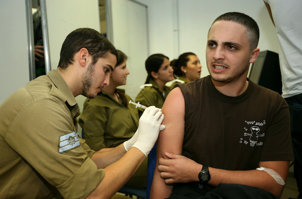 Illustrative photo of an Israeli recruit receiving a painful vaccine injection on his first day of military service. November 23, 2008. (Moshe Shai/Flash90)