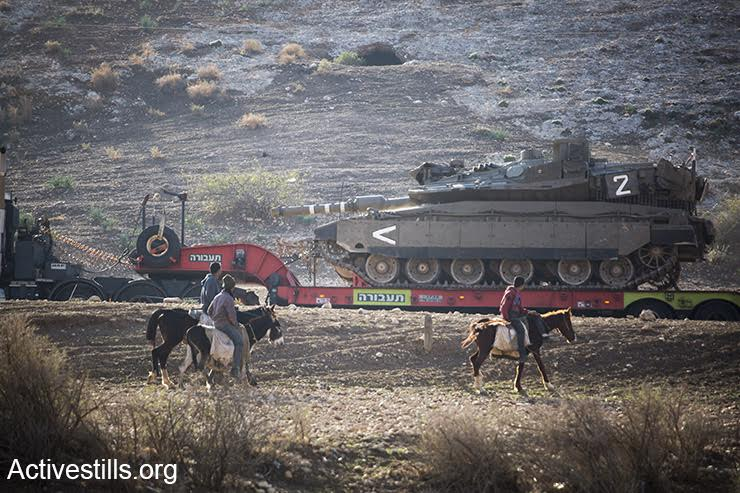 Palestinians on horseback watch as an Israeli tank is carried toward the 'open-fire zone' in the Jordan Valley, West Bank, December 8, 2016. (Keren Manor/Activestills.org)