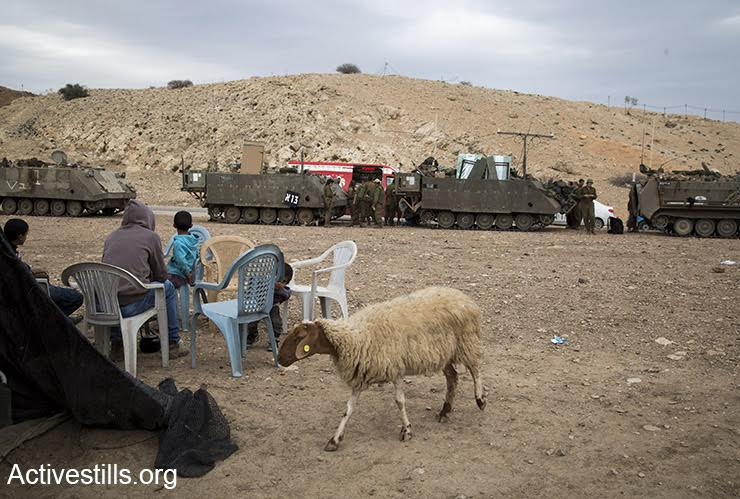 Palestinians look on at an army training exercise in the Jordan Valley, West Bank, December 8, 2016. (Keren Manor/Activestills)