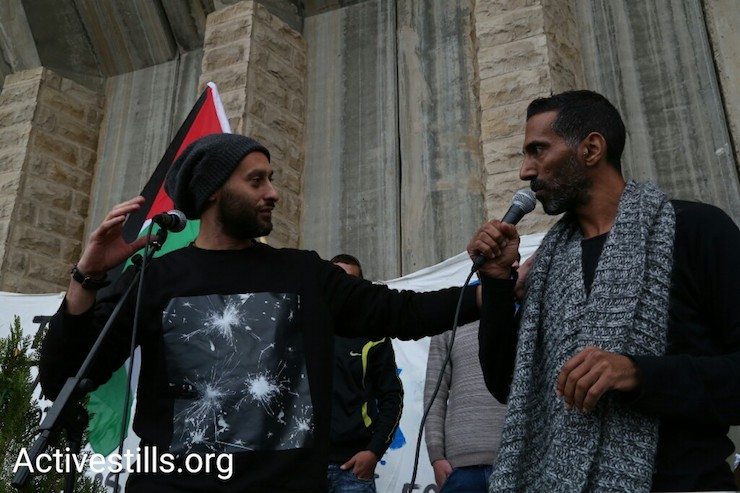 "Palestinian rapper Tamer Nafar (R) and Israeli spoken word artist Yossi Tzabari (L) perform ""Ana mish politi"" (I Am Not Political) during a demonstration along Route 60, West Bank, December 16, 2016. (Keren Manor/Activestills)"