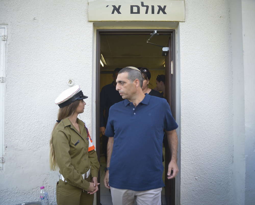 Ofek Buchris passes a young military policewoman as he leaves the Jaffa Military Court, September 29, 2016. (Flash90)