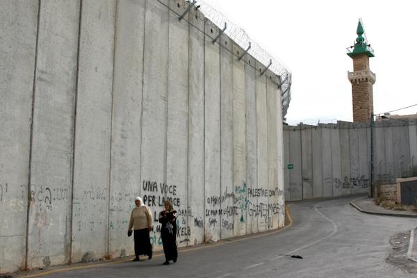 Two Palestinian women walk along Israel's separation wall in the West Bank village of Abu Dis. (Anna Kaplan/Flash90)