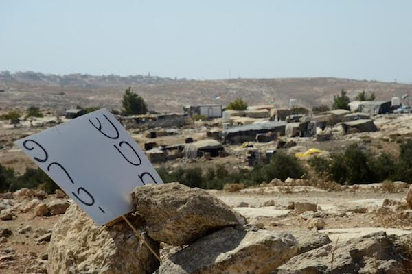 A sign in Hebrew reads 'private territory,' with Susiya in the background, south Hebron Hills, West Bank, October 2016. (Gili Getz)