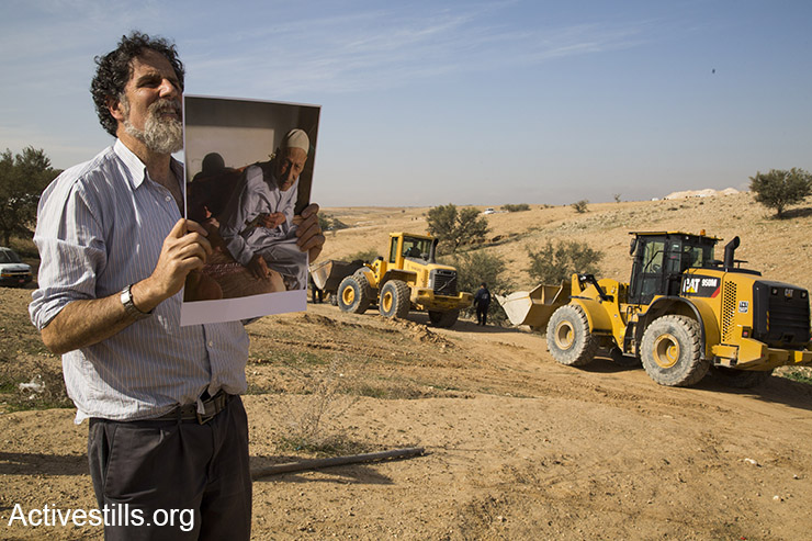 Rabbi Arik Ascherman holds up a photo of a 100-year-old resident of Umm el-Hiran whose home was slated for demolition, as bulldozers enter the village behind him, January 18, 2017. (Keren Manor/Activestills)